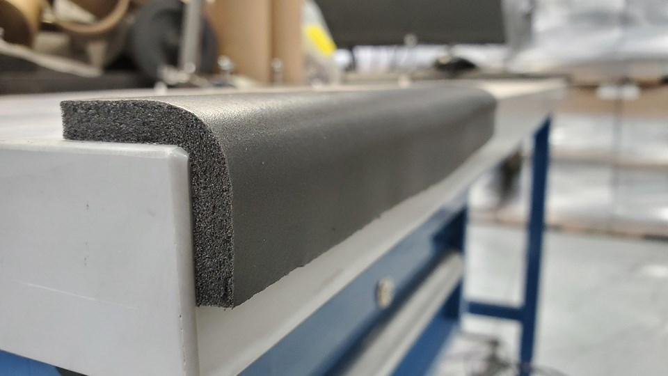 Black foam bonded across a corner of a workbench